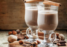 Hot cocoa with cinnamon, chocolate and nuts, selective focus